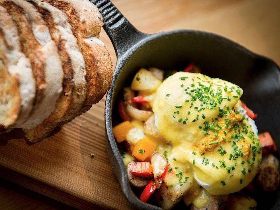 Skillet with potatoes, eggs benedict, and bread.